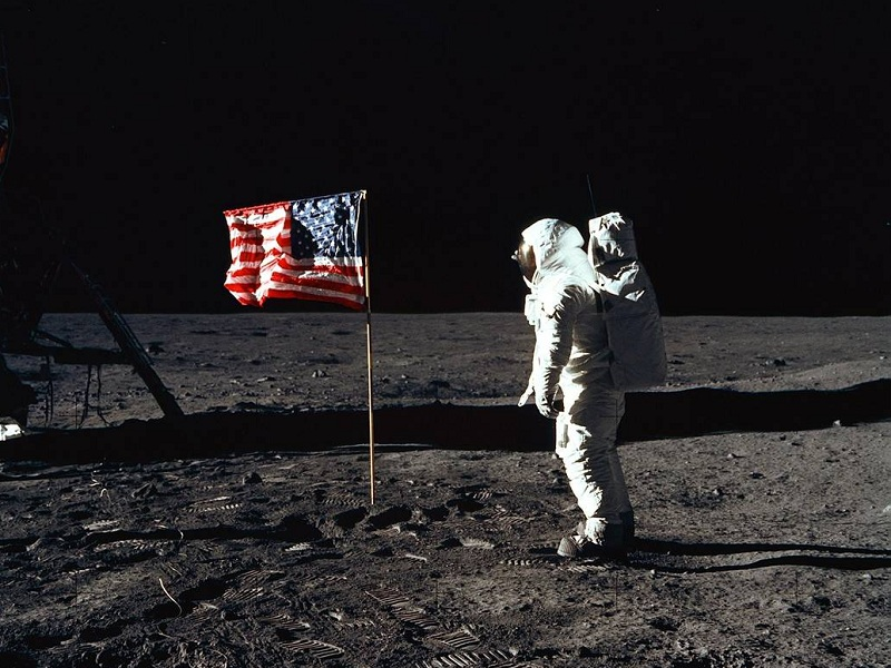 Astronaut Edwin E. Aldrin Jr. poses for a photo beside the American flag