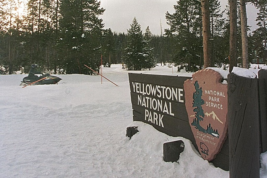 A Snowmobile Rides Past The Entrance Of Yellowstone National Park