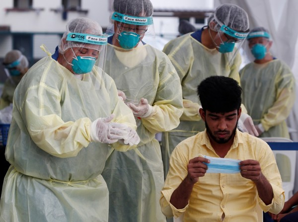 Medical workers prepare to perform a nose swab on a migrant worker at a dormitory, amid the coronavirus disease (COVID-19) outbreak in Singapore