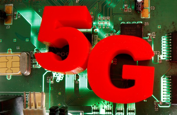 3D-printed objects representing 5G are put on a motherboard in this picture illustration