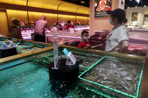 Customers are seen at a live seafood section inside a supermarket, following a new outbreak of the coronavirus disease (COVID-19), in Beijing