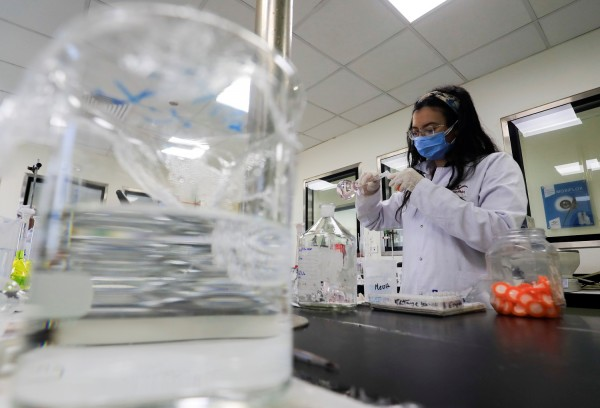 A pharmacist doctor works on the basics of the raw materials for investigational of the coronavirus disease (COVID-19) treatment drug