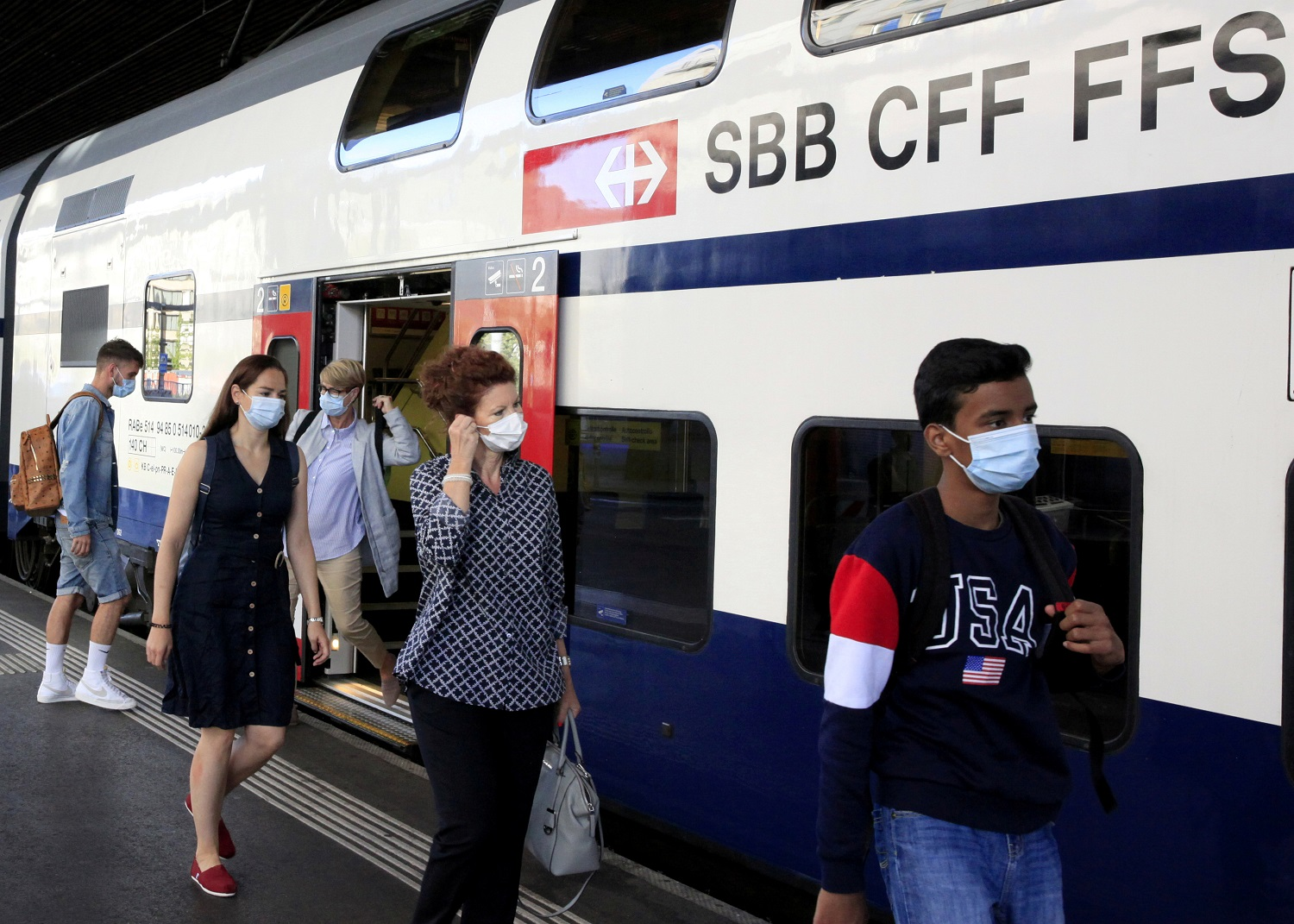 Passengers wear protective masks as they leave a train of Swiss railway operator SBB in Zurich, Switzerland
