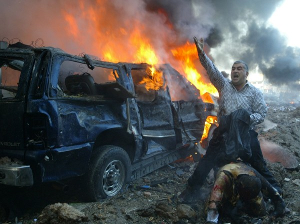 A Lebanese man shouts for help for a wounded man near the site of a car bomb explosion in Beirut