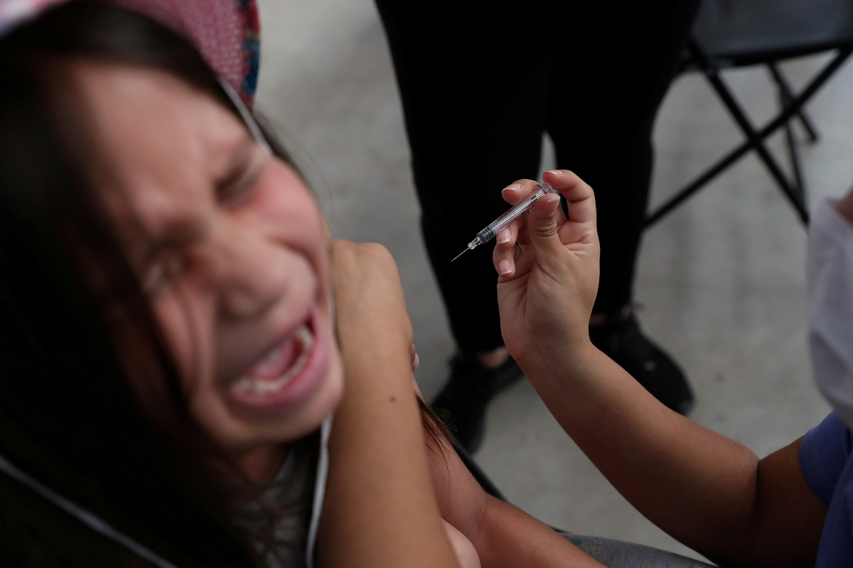 A child receives a vaccination as part of the start of the seasonal flu vaccination campaign as a preventive measure due to the outbreak of coronavirus disease (COVID-19), in Santiago