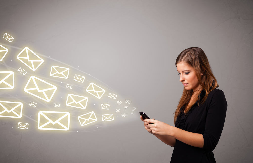Attractive young lady holding a phone with message icons — Stock Image