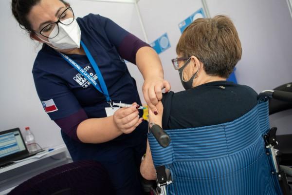 A health worker administers a COVID-19 vaccine to a senior citizen at Estadio Bicentenario de la Florida vaccination centre