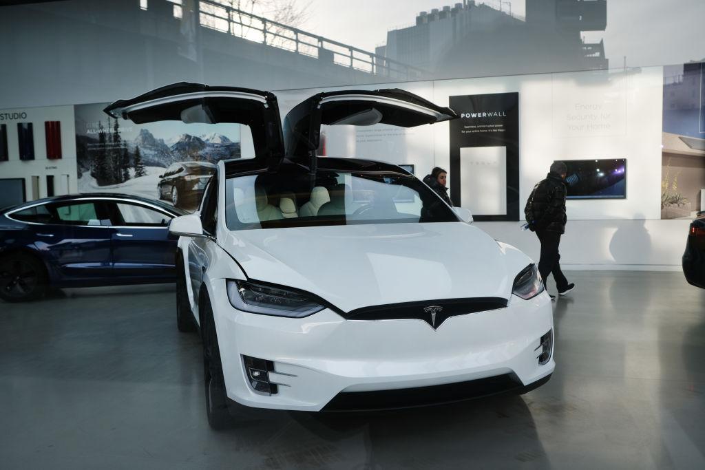 A Tesla vehicle is displayed in a Manhattan dealership
