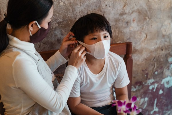 Woman Putting a Face Mask on a Child